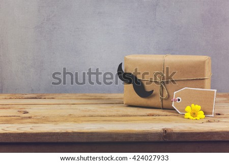 Gift box and gift tag on wooden table. Father's day holiday background.  - stock photo