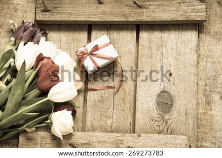 Gift box and tulips on a wooden background - stock photo
