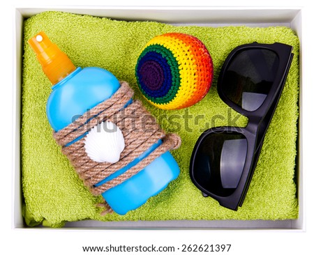 Gift box - blue plastic bottle of some liquid cosmetics, black sunglasses, ball for footbag game are on green towel. Decorated with rope and shell. Isolated. - stock photo