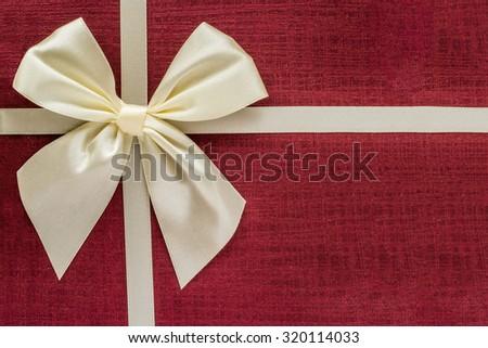 Gift box closeup, burgundy paper background and ribbon - stock photo