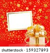 Gift box in gold wrapping paper on a beautiful red abstract background - stock photo