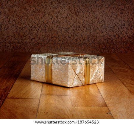 Gift box in gold wrapping paper with ribbon on wooden table - stock photo
