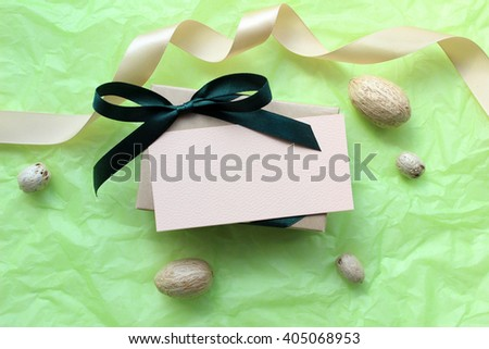 Gift box Mockup with a blank card. Bow, ribbon and elements of decor. Light green wrapping paper background. Eco design, natural products, hand-made products. - stock photo