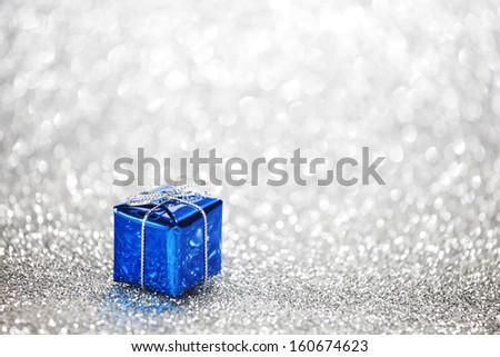 Gift box on glitter silver background - stock photo