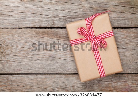Gift box on wooden table background with copy space - stock photo