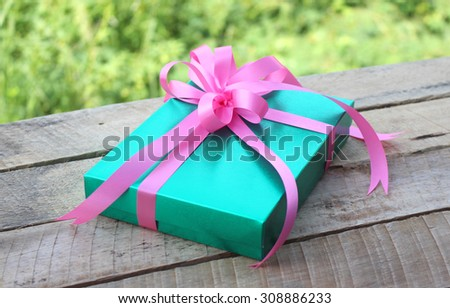 gift box on wooden table on natural sunny background - stock photo
