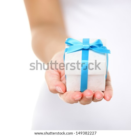 Gift box / present or christmas gift hand close up. Decorative gift box tied with a turquoise ribbon and bow carefully cupped in female hands as she gives a surprise present to a loved one. Isolated. - stock photo