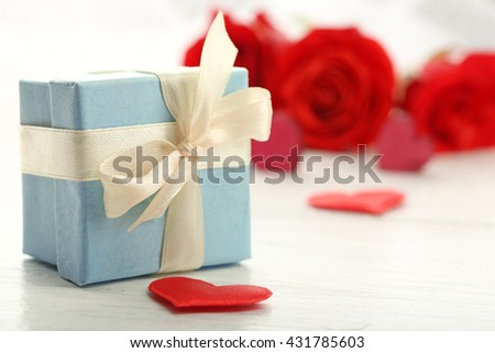Gift box, rose flowers and decorative hearts on light wooden background - stock photo