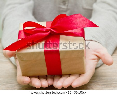 gift box tied with a red ribbon in the hands - stock photo