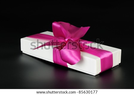 Gift box with a big pink bow. On a dark background. - stock photo