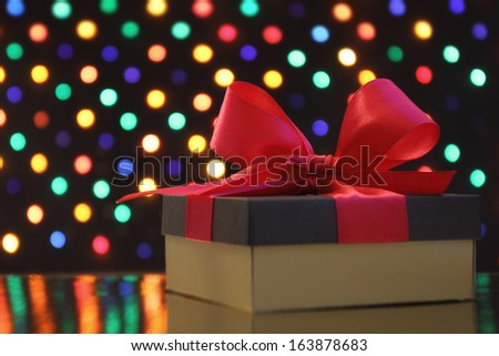 Gift box with a bow in front of a festive garland lights soft-focus background - stock photo