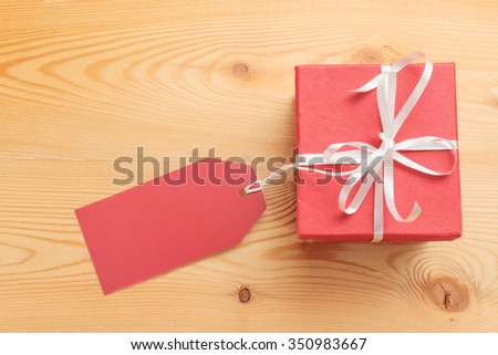 Gift box with blank red paper tag on wooden background. Top view - stock photo
