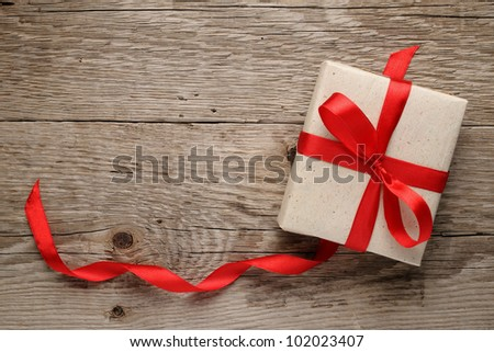 Gift box with bow on wooden background - stock photo