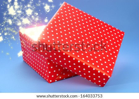 Gift box with bright light on it on blue background - stock photo