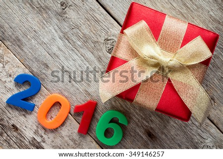 Gift box with gold ribbon  and a 2016 sign on wooden background - stock photo