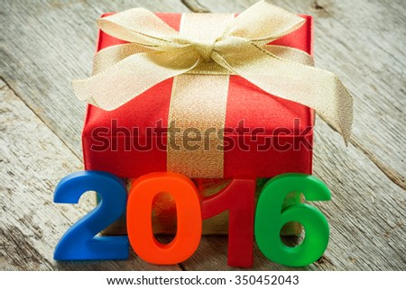 Gift box with golden ribbon and a 2016 sign on wooden background - stock photo