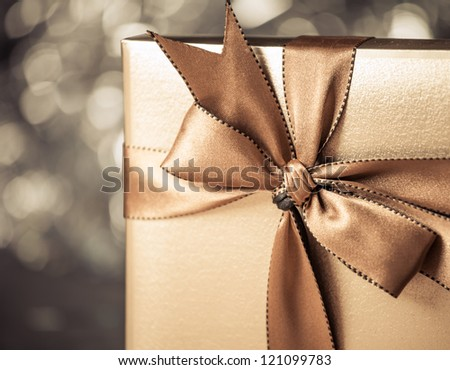 gift box with golden ribbon, glittery gold background - stock photo