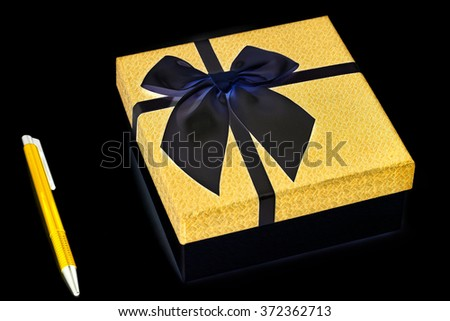 Gift Box with pen on black background - stock photo