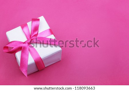 gift box with pink ribbon on pink background - stock photo