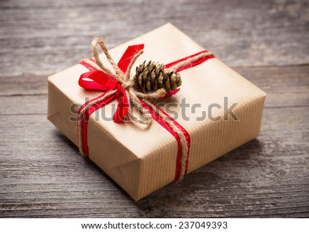 Gift box with red bow and cone on wooden table - stock photo