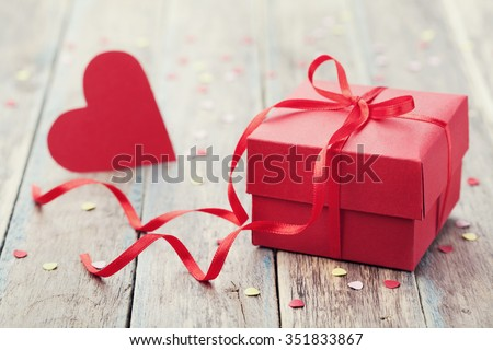 Gift box with red bow ribbon and paper heart on wooden background for Valentines day - stock photo