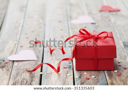 Gift box with red bow ribbon and paper heart on wooden table for Valentines day - stock photo