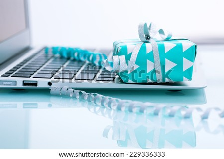 Gift box with silver bow on light background next to the computer. On line shopping - stock photo
