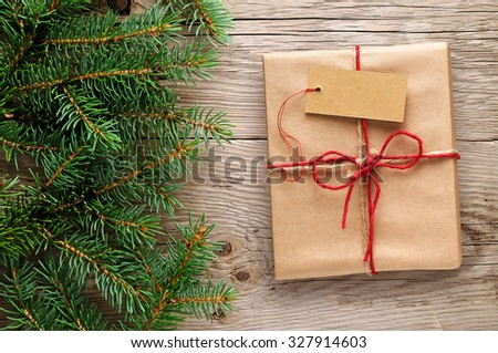 Gift box with tag and fir branches on wooden background - stock photo