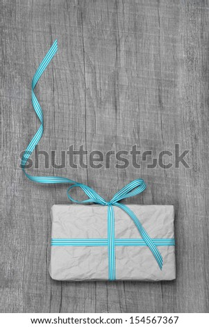 Gift box with turquoise striped ribbon for anniversary or christmas - stock photo