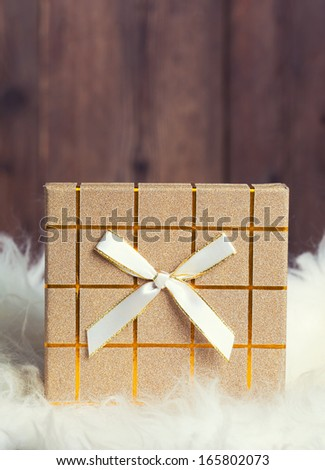 gift box with white fur on wooden background - stock photo