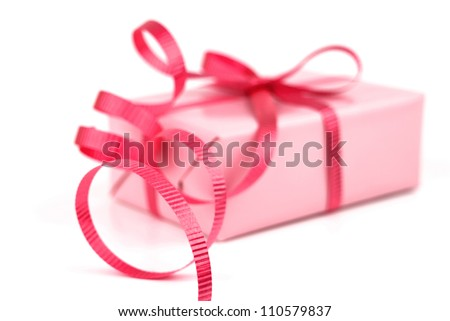 Gift box wrapped in pink wrapping paper and red curly ribbon isolated on white background. - stock photo