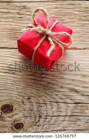 Gift box wrapped in red paper on wooden background - stock photo