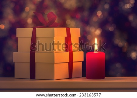 Gift boxes and candle against defocused lights - stock photo