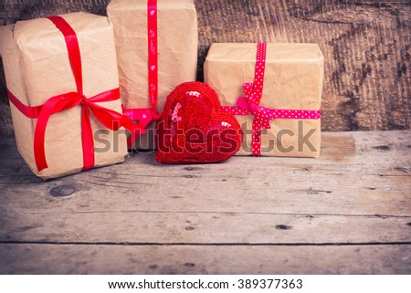 Gift boxes  and decorative red  heart on  vintage  wooden background. Selective focus. Place for text. Toned image. - stock photo