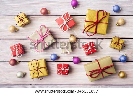 Gift boxes and xmas decoration over wooden background - stock photo
