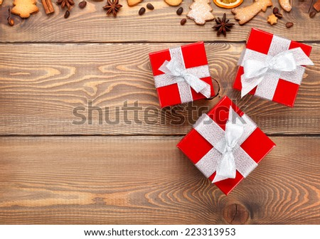 Gift boxes over christmas wooden background with spices, gingerbread cookies and copy space - stock photo