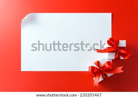 Gift boxes with blank card on red background - stock photo