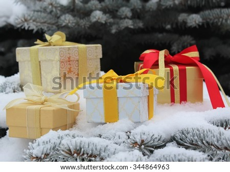 Gift boxes with bows on fir-tree branches in snow - stock photo