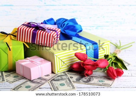 Gift boxes with money and flowers on color wooden background - stock photo