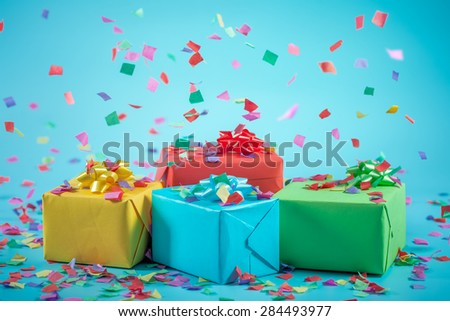 Gift boxes with paper confetti on blue background - stock photo