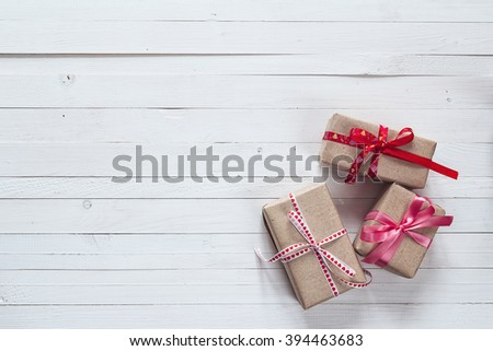 Gift boxes with red ribbons on a white painted wooden background and empty space for text. Top view with copy space - stock photo