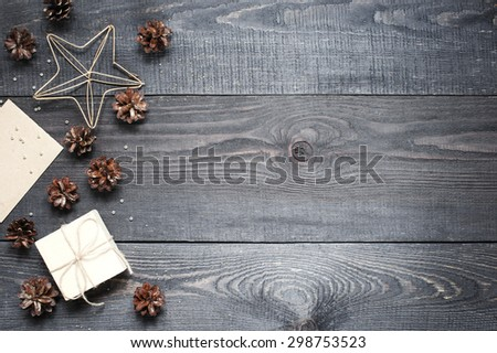Gift, card, pine cones, metal star on the dark wooden textured table - stock photo
