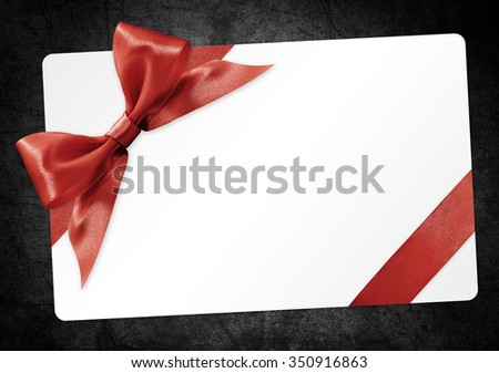 gift card with red ribbon bow Isolated on black grunge background - stock photo