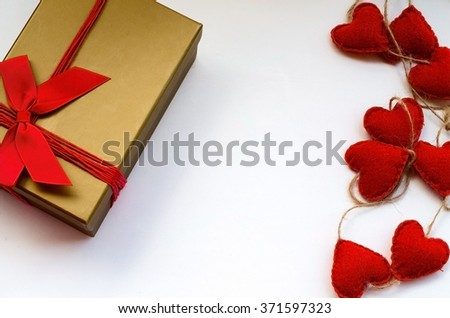 Gift gold box with red bow and hearts on white  background for Valentines day - stock photo