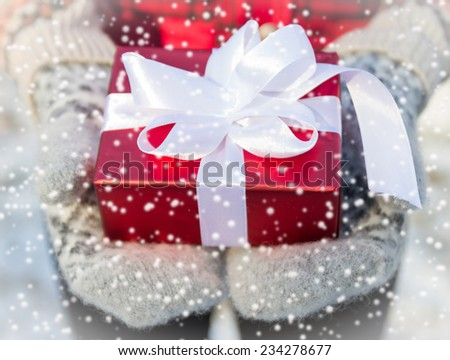 gift in hands on mittens on winter background  - stock photo