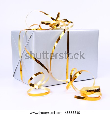 Gift in silver wrapping with gold bow on white background - stock photo