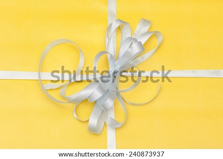 gift in yellow packing with a white bow - stock photo