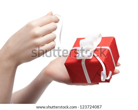 Gift opening. Wrapped in red paper present with white bow, isolated on white - stock photo