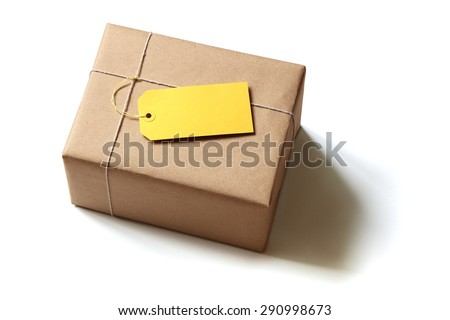 Gift package wrapped in brown recycled paper with blank yellow label isolated on white - stock photo