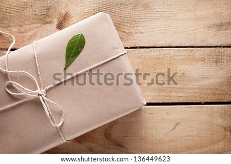 gift package wrapped with paper and rope with a leaf on wooden background - stock photo